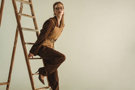 attractive model in retro style posing near wooden ladder isolated on beige