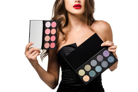 cropped view of girl with red lips holding palettes with eyeshadows isolated on white