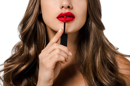 cropped view of girl with long hair applying red liquid lipstick isolated on white
