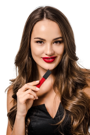 beautiful girl smiling, looking at camera and holding red liquid lipstick isolated on white