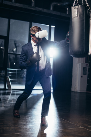 businessman in suit and virtual reality headset boxing in gym