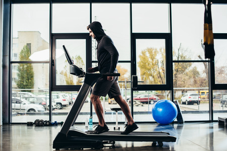side view of handsome sportsman in hoodie exercising on treadmill in gym