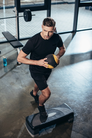 high angle view of handsome sportsman training on step platform with medicine ball in gym Фото со стока