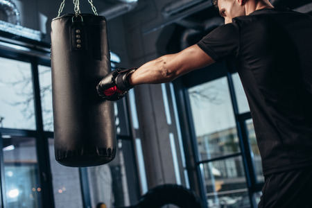 side view of handsome boxer training with punching bag in gym