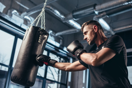 low angle view of handsome boxer training with punching bag in gym