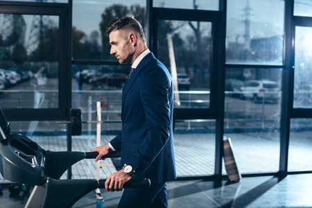 side view of handsome businessman in suit exercising on treadmill in gym