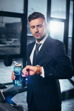 handsome businessman in suit exercising on treadmill, holding sport bottle and checking time in gym