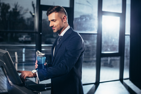 handsome businessman in suit exercising on treadmill and holding sport bottle in gym