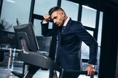side view of tired handsome businessman in suit exercising on treadmill in gym