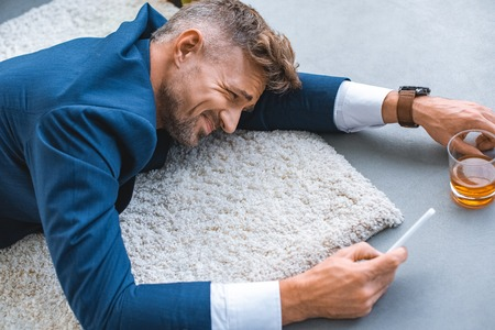 drunk businessman lying on carpet with smartphone in hand