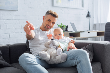 smiling father sitting on couch with baby daughter and pointing with finger at something Stock Photo