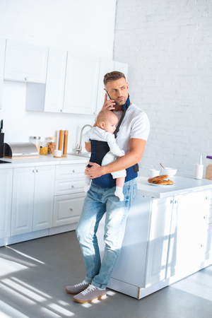 serious father holding infant daughter in baby carrier and talking on smartphone