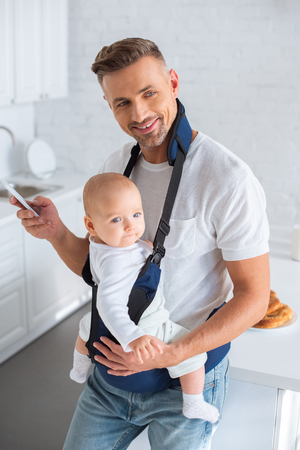 cheerful father using smartphone and holding infant daughter in baby carrier