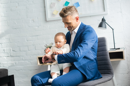 handsome businessman showing watch to infant daughter in room