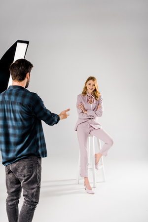 back view of young photographer talking with beautiful smiling female model in studio