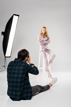 back view of photographer sitting and photographing beautiful female model posing in studio 스톡 콘텐츠