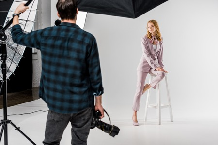 back view of photographer holding camera and model posing in studio