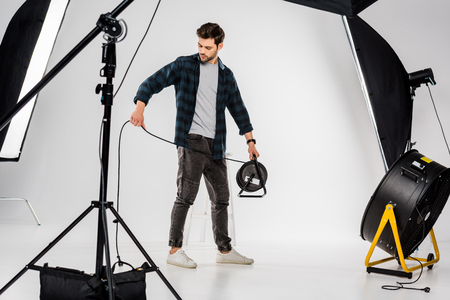 young photographer working with equipment in professional photo studio