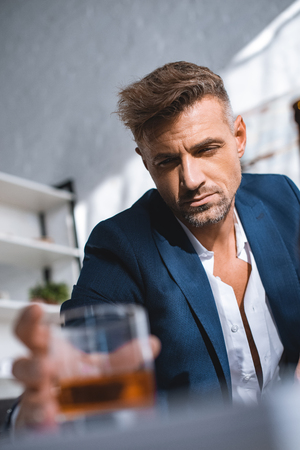 selective focus of drunk businessman holding glass of whiskey