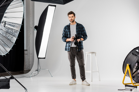 handsome young photographer holding professional camera and looking at camera in photo studio Stock fotó