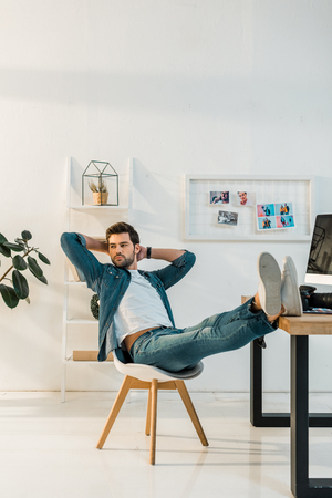 relaxed young retoucher sitting with hands behind head and legs on work desk