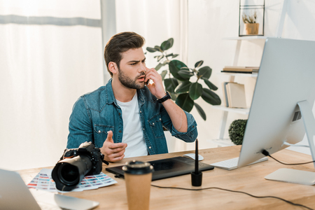 serious young retoucher talking by smartphone and using desktop computer with drawing tablet at workplace Stock Photo