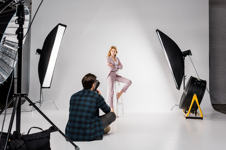 back view of young photographer shooting beautiful female model in studio 스톡 콘텐츠