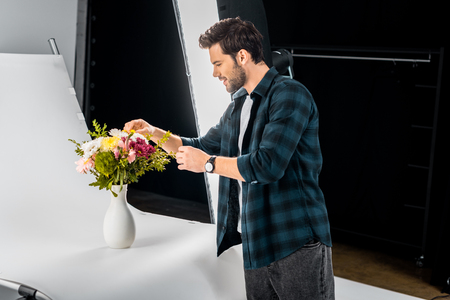 smiling young photographer arranging flowers in photo studio