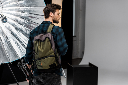 back view of young man with backpack holding professional equipment and looking away in photo studio 스톡 콘텐츠