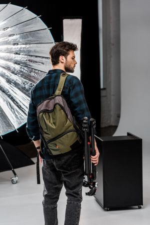 back view of young man with backpack holding professional equipment in photo studio 스톡 콘텐츠
