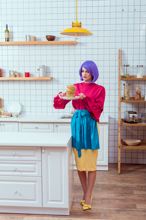 beautiful housewife in colorful clothes with purple hair holding plate with pancakes in kitchen