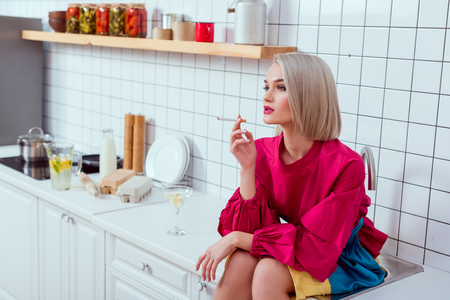 selective focus of beautiful fashionable woman sitting on kitchen counter and smoking cigarette 免版税图像