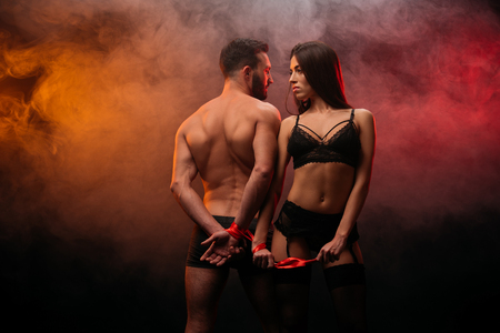 beautiful passionate couple with red ribbon in smoky room