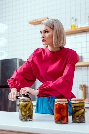 selective focus of beautiful stylish housewife sealing jar of pickled cucumbers in kitchen Reklamní fotografie