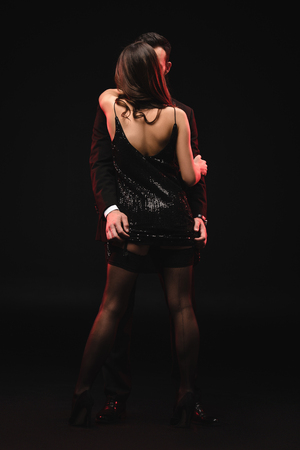 vue arrière d'un couple séduisant s'embrassant dans une pièce sombre Banque d'images