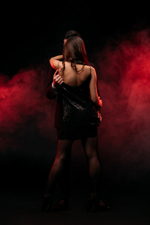 rear view of sexy couple hugging in red smoky room Фото со стока