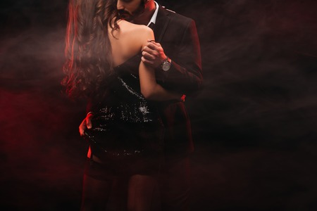 cropped view of passionate couple hugging in red smoky room Stockfoto