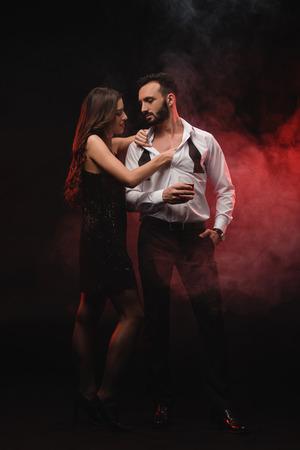 femme passionnée étreignant l'homme avec un verre de whisky dans une pièce enfumée rouge