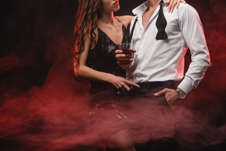 cropped view of sexy woman hugging man with glass of whiskey in red smoky room 스톡 콘텐츠
