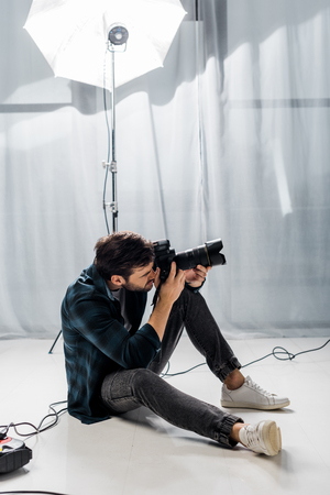 handsome young photographer with professional camera taking pictures in studio