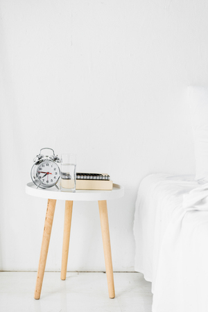 alarm clock and books on table near bed