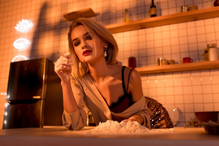 beautiful housewife smoking cigarette and looking at camera while cooking in kitchen with orange light