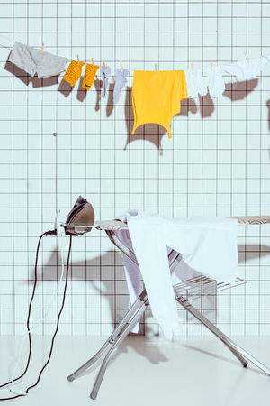 hanging clothes and ironing board with white tile on background in bathroom