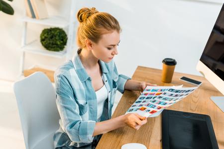 vue grand angle d'un jeune retoucheur travaillant avec des photos au bureau Banque d'images