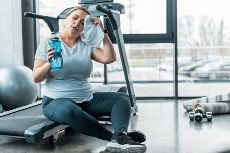 tired plus size woman wiping sweat with towel while sitting on treadmill and holding bottle with water Reklamní fotografie