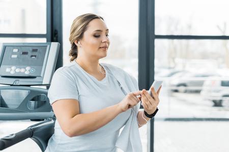 Attraktives übergewichtiges Mädchen, das Smartphone hält, während es Musik in Kopfhörern hört