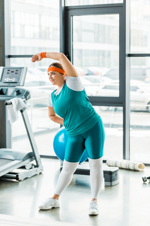 cheerful overweight woman exercising in sportswear in gym