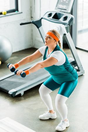 overhead view of serious plus size woman training with dumbbells