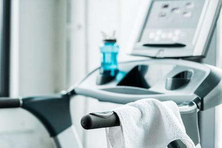 selective focus of white towel hanging on modern treadmill in gym Zdjęcie Seryjne
