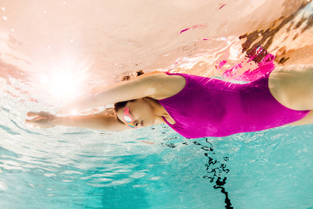 focused woman swimming in goggles underwater in swimming pool Stockfoto